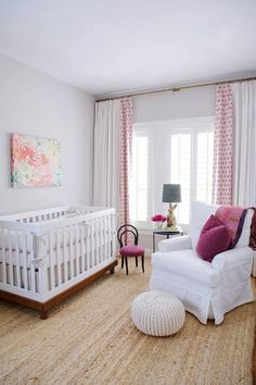 This gorgeous white and purple nursery boasts a two tone crib dressed in white bedding and placed beneath a pink and green canvas art piece hung from a gray wall positioned adjacent to a window covered with white and pink curtains.