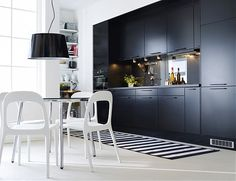 black kitchen cabinets and white dining chairs