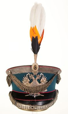 AN IMPERIAL RUSSIAN ENGINEER OFFICER'S SHAKO OR KIVER. Model 1907 'Bell crown' style shako of black leather with royal blue wool rise and black band, piped in red, and black leather visor, with silvered eagle plate with crossed axes, nickel chin scales and visor trim. Complete with silver bullion crown braid and cords, cockade and feather plume in the Romanov colors. Lined in cotton and leather with a maker's label embossed in the crown. - Jackson's International Auctioneers and Appraisers