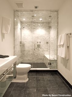 A masculine bathroom that features a spacious shower, floating steel and glass vanity and black marble tile floors. We especially love the dramatic calacutta marble shower, which gives this man's bathroom a cool, but not too cold, look. #Marble #Masculine