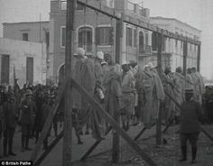 This shocking sight is from 1911 footage during the Italo–Turkish War.  There is not any information on what crimes these men were supposed to have committed or their identity.  Italian authorities adopted many tyrannical methods against the rebels, such as public hangings as a retaliation for ambushes
