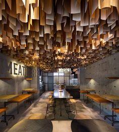 faux plafond bois suspendu et parement mural en béton d'un restaurant haut de…