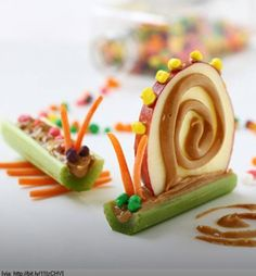 Love the snail! Use Nerds, Peanut Butter, Carrots (Or maybe stick pretzels), on apple and celery.