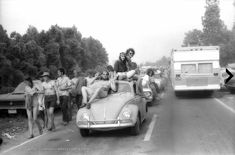 Carter Tomassi photos that appeared in The Great Speckled Bird. Three people riding outside a VW Bug on the way to the Atlanta Pop Festival in 1970