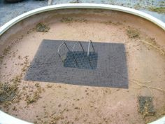 Covering the drainage holes with mesh to stop the soil washing away