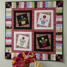 Painted Posies -- Love the boarder    Quilt by Erinn Kennedy and Susan Sochacki.  Machine Quilted by Jessica Brunnemer.    This quilt with is fresh-as-a-daisy posies in cute pots tilted this way and that, looks like it might be a lot of work, but it's not. Make four blocks add sashing and borders, and you'll have a new quilt to brighten your wall.