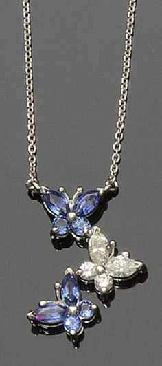A sapphire and diamond pendant necklace. Designed as a trio of butterflies, alternately set with navette and circular-cut sapphires and diamonds, on a fine trace-link back chain, the pendant reverse stamped 'Pt 950', pendant length 2cm, chain length 42cm.