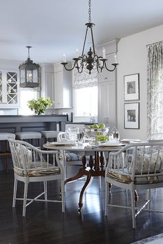 Beautiful dining room with round vintage dining table, white faux bamboo chairs from Old Things Past - Toronto with seat cushions upholstered in Kravet Ranjani Shale, pillows in Kravet Pop Flower Birch, Kravet Sanabelle Driftwood Curtains window panels & roman shade.    Para Paints Jetstream