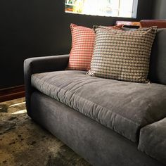 The Alexandra Sofa posing in masculine clothing. Fitted upholstery, suede-like fabric, charcoal grey, geometric pattern, mono tone rug. Hudson Furniture, Sofa, Couch, Zimbabwe, Bespoke, Love Seat, Charcoal, Upholstery, Furniture Design