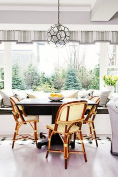 Black table, yellow and white woven chairs, white bench with a grey cushion, printed yellow, black and white throw pillows, grey curtains, and circular light fixture