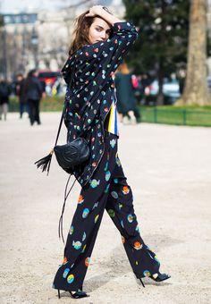 Zuzanna Bijoch wears a Stella McCartney jumpsuit, printed jacket, Gucci bag, and black heels