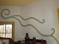 Bas relief wall sculpture vine with glauconite and lime natural pigment; sculpted on straw bale wall.