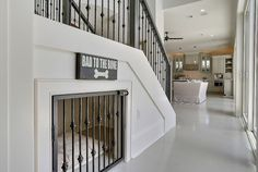 great use of under stairway space <3 matched iron stair rail & kennel door