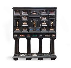Curiosity Cabinet, Cabinet base strongly molded wood , blackened and inlaid polychrome marbles such as lapis lazuli , Ruin marble , sea green, rosso antico , large antique. It presents an architectural façade opening with three drawers and doors pediment with niches with antique gold metal characters . The drawer fronts are set with marbles in frameworks . The sides have a diamond pattern and triangles. It is based on a vertical base supported by a base decorated with recessed marble slabs…