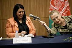This Year's Best Political Photos- U.S. Secretary of State Hillary Rodham Clinton, right, helps Samira Hamidi, an Afghan citizen, with a microphone during the Afghan Civil Society event at the Okura Hotel Center in Tokyo, Sunday, July 8, 2012. (AP Photo/Brendan Smialowski, Pool)