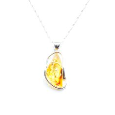 Stunning, natural baltic amber pendant. This golden, clear stone is surrouned by a minimalistic, modern silver frame and comes with a double twist sterling silver chain.The Amber stones have been sculpted for centuries by the everlasting waves of the Baltic Sea, and are hand picked just off the shores of Poland.