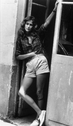 Lauren Hutton- Plaid long sleeve button-up tucked and belted into high-waisted shorts worn with white sneakers