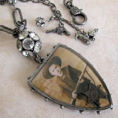 "Cowboy Necklace  glass shield pendant that is two sided with vintage images; one child cowboy and one horse portrait. A small Deputy U.S. Marshal badge attached, and from the chain a dangling gun, crystal ball and horse. A very special piece sure to get attention.  23"" long $58.00"
