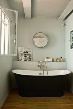 Une baignoire à l'ancienne dans cette salle de bains aux murs clairs