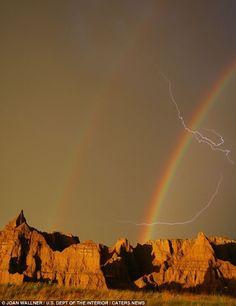 a bolt of lightning cracking through a double rainbow above Badlands National Park in South Dakota
