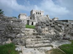 "View of Mayan ruins, Tulum, Cozumel, Mexico. The trading city of Tulum was built on a stone outcrop on the edge of the Caribbean Sea. Pictured are ""El Castillo"" on the right, and ""The Temple of the Descending God"" on the left. The Descending god is the main god honored at the site. The majority of the present day ruins were built between 1200 and 1500 CE."