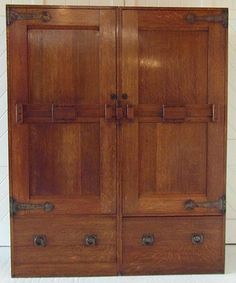 Arts & Crafts double wardrobe in oak with steel strap hinges with superbly designed heavy sliding wooden door latches. Two large bottom drawers with iron handles. This wardrobe bears strong design influences used by C.R. Ashbee's Guild of Handicraft.  Attributed to C.R.Ashbee  Circa 1895