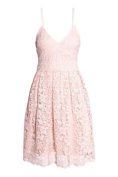 Een knielange jurk van opengewerkt, geborduurd kant met smalle, verstelbare schouderbandjes, een V-hals, een naad in de taille en een klokkende rok. Blinde