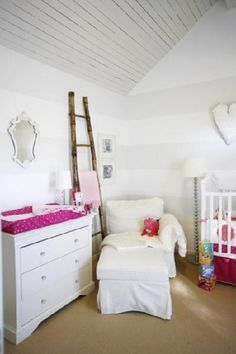 adorable white & pink girl's nursery design with white & gray striped walls. White slip-covered chaise lounge, white dresser changing table, white ornate mirror, glass lamp, decorative ladder, white crib, chrome floor lamp, white & pink polka dot changing table cushion and white & pink bedding. white pink nursery colors.