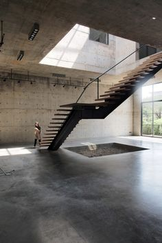 Thai studio ASWA has placed a four-storey atrium with a huge gridded skylight at the centre of this concrete art gallery and studio in Bangkok.