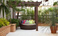 Ao lado desta pérgola, vaso de barro com dasilirium. O jardim também conta com jasmim-dos-poetas e, em primeiro plano, à esq., helicônias seguidas de xanadu, palmeira-fênix e orquídeas-bambu. Projeto da arquiteta paisagista Greice Peralta
