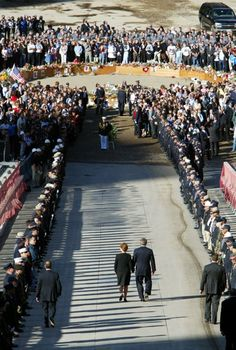 """U.S. President George W. Bush and first lady Laura Bush walk past an honor guard as they proceed down the ramp into the pit at the site of the World Trade Center in New York September 11, 2002. Bush is visiting all three disaster sites in Washington, Pennsylvania and Washington on the one year anniversary of the attacks, and cautioned Americans that the United States has """"determined enemies"""" and that the country is """"not invulnerable to their attacks."""" (REUTERS/Shaun Best GMH/GN)"""