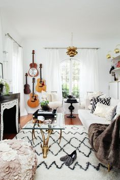 eclectic livingroom: brass lighting, white sofa, hanging guitars, Moroccan rug & glass coffee table #homedecor #interiordesign