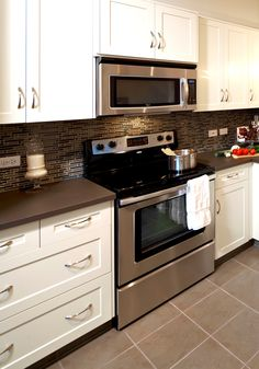 White shaker-style cupboards and dark countertops with glass tile backsplash and stainless steel appliances at Prospect Ridge by Avi Urban