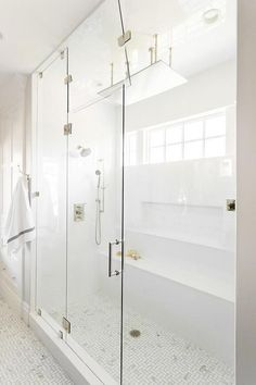Gorgeous long steam shower is fitted with a seamless glass enclosure and marble maze floor tiles accenting white subway surround tiles fitted with polished nickel shower heads as a rectangular rain shower head hangs over a long bench positioned beneath a tiled niche.