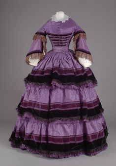 ca 1860s Material purple silk, black and purple velvet. Skirt is a full hoop skirt of 3 superimposed tiers of (1) purple silk (2) bands of purple silk and velvet (3) black velvet (4) black fringe and (5) purple fringe. All over purple silk skirt fully lined (metal hooks at waist band) pleated in back - tight tucks in front of waist band Bodice is high round neck - open sleeves - square waist - purple silk with 10 ball buttons ...