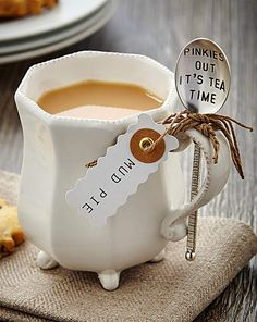 Footed ceramic mug which features beaded rim and stamped sentiment spoon cleverly tucked into a slotted handle for storing. Spoon reads 'Pinkies Out It's Tea Time'.