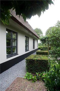 Mooie tuin met oude bestrating, grijs grind en vierkante struiken en leibomen. Past mooi bij wit huis.