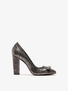 Zapato de tacón elaborado en vacuno. El diseño presenta un acabado craquelado con detalle de flecos en pala. Forro y planta en caprino con detalles de vivos en piel de corte. Piso con detalle de ruleta.