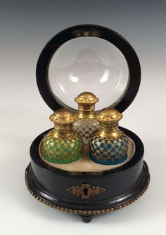 PALAIS ROYALE PERFUME CASKET c1885 Palais Royale circular perfume casket with glass domed top which opens to three opaline glass perfume bottles with ormolu mounts, one white, one green and the other blue.