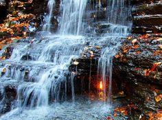 """Um velho mistério segue assombrando os visitantes do Chestnut Ridge Park, em Nova York. Como pode haver uma chama eterna embaixo das quedas de uma cachoeira? Este mito é o que batiza a cachoeira: Eternal Flame Falls (Quedas da Chama Eterna, em tradução literal). Mas o fenômeno é simplesmente um vazamento de gás natural que gera o fogo. E, na verdade, a chama não é exatamente """"eterna"""", ela simplesmente surge de vez em quando. Mas o impacto causado em quem presencia a cena, bom, isso é uma…"""
