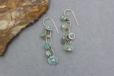 These earrings are long and have a very Bohemian feel. The beads are made from pieces of Ancient Roman Glass found in Afghanistan. These beads have gorgeous pitting, patina and iridescence from being buried in the ground for a thousand years. The glass is in pale blue, aqua and green shades. I made a small fine silver chain to dangle the glass from. All of the silver has some patina. These earrings hang approximately 2 1/2 long.