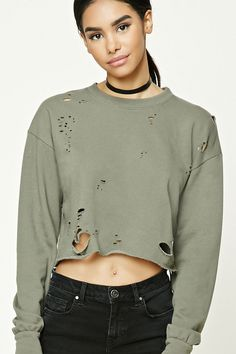 A French terry knit sweatshirt featuring an allover distressed design, a raw-cut cropped hem, a crew neckline, and long dropped sleeves.