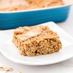 Straight view of a square piece of healthy peanut butter banana baked oatmeal on a white plate with the baking pan in the background