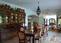 A sala de jantar em madeira bruta conta com um armário alto, que abriga uma coleção de moringas de barro e pratos coloridos – souvenirs adquiridos pelo proprietário em suas viagens.