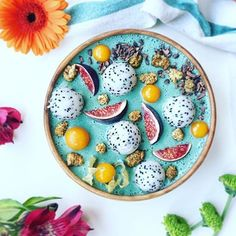 This beautiful Smoothie Bowl is by @$dailybowlofhappiness It's a blend of banana-pineapple-kale and spirulina topped with dragon fruit balls, physalis, fresh figs, dried mulberries and cocoa nibs