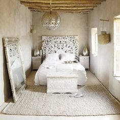 Love the mix of intricate such as the headboard and mirror and earthy such as the wicker basket and wood ceiling.