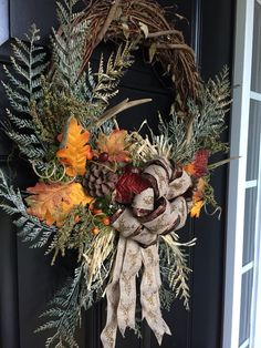 Rustic autumn grape vine wreath with deer antlers,  leaves, pine cones, and ribbon