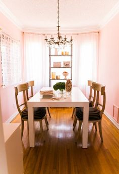 The pink walls and drapes make this dining room so romantic.