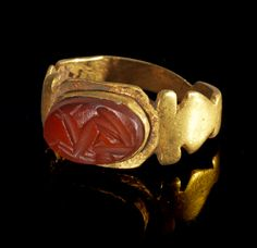 Golden ring with gemstone of red cornelian depicting an animal with horns coming out of a calyx. Roman, 2nd - 3rd century A.D.