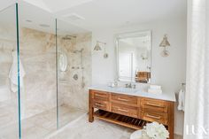 Master bathroom features an extra long stained oak vanity with shelf topped with white quartz under a beveled mirror illuminated by polished nickel swing arm sconces situated next to a spacious walk in shower clad in beige tile and two shower heads.